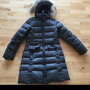 Dunfrakke blød varm vinter frakke koks grå med pels på hætten sælges.Der er lille mærke i nylon foran men ikke bemærkelsesværdigt. Lille hul i for i jakke lommen. Np 3400kr