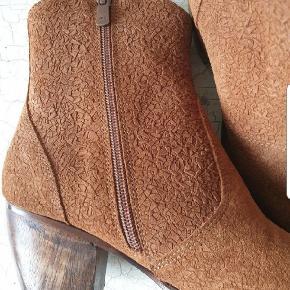 Ny Smuk western støvlet i cognac med flot prægning i skindet. Den er i skind inde og ude, lædersål og blød gummi under forfod og hæl.  Str 37, til en normal fod og plads til vrist.  Se også mine mange andre sko og tøj, smykker under profilen
