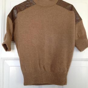 """Varetype: Sweater Farve: Lysebrun  Flot sweater med """"skulder-lapper"""" fra Topshop. Sweateren er lavet af 48% bomuld, 27% uld og 25% nylon. """"Lapperne"""" er lavet af 51% viskose og 49% polyester. Sweateren er brugt, men stadig i rigtig god stand.  Jeg bytter ikke.  Ved TS-handel lægges 5% oveni prisen.  Køber betaler porto. Sweateren sendes som almindeligt brev via Post Danmark, eller via DAO for 37 kr."""