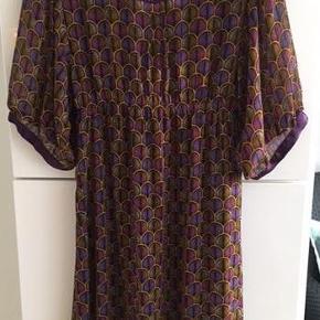 """Brand: Snob Varetype: Snob kjole Farve: Se billede  Fin """"vintage look"""" kjole i 2 lag fra Snob by sans noblesse.  Underkjolen er i et gennemsigtigt stof i en smuk dyb lilla farve.  Yderstoffet har et smukt mønster i farverne lilla, dybrosa og bronzefarvet. Der er en skjult lynlås i venstre side af kjolen.  L: 96 cm.  OBS! Jeg sælger også nogle smukke pels stolaer i Tibetlam samt en pelsvest fra Ambre Babzoe, som passer rigtig godt til denne kjole.  Se også mine andre kjoler annoncer her på Trendsales fra bl.a. Oxmo, Vila, E, 2Biz, Container, Nümph, Simiti."""