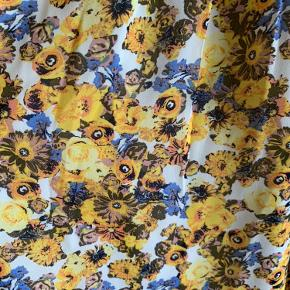 Gul/blå blomstret kjole fra Vila. Aldrig brugt, vasket én gang i neutral vaskemiddel. Knaplukning foran ved brystet og elastik i taljen.