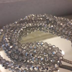 Ubrugt armbånd med små klare perler og perler i matsølv, som gør det glimter flot i solen. Omkreds kan max. blive ca. 19 cm.