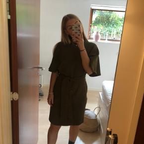 """Sælger Army grøn Ganni kjole. Den er brugt i alt 3 gange og er derfor så god som ny. Sælger da jeg ikke får den brugt. Modellen minder meget om """"Ganni Recycled Heavy Crepe""""."""