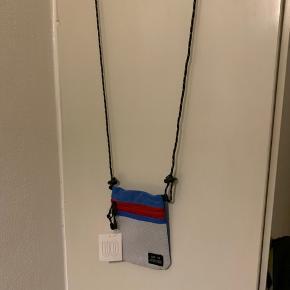 Lille unisex taske med regulerbar snor rem fra UO. Mix af farverne (rød, hvid, koboltblå) Model har to lynlås rum foran og lille knap rum bagpå. Mål: Højde ca 15 cm og bredde ca 11-11,5 cm Snor rem kan max blive knap 109-110 cm. Materiale r sports poly. (Kan sendes for 20 via postnord som brevpost)