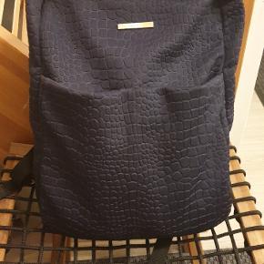 DAY et Birger Mikkelsen rygsæk / taske / computertaske / skoletaske. Meget rummelig: højde 40 cm, bredde 33 cm. Er som ny. Købt foråret 2018. Kan ikke finde den på nettet, så ved ikke om man kan købe den mere. Der er et computerrum inde i tasken, og ro små rum inde i tasken, samt et lille udvendigt og to lommer foran på tasken. Mørkeblåt stof med flot mønster og med flotte guld detaljer. Nypris var 1100 kr. Prisidé er 700 kr. Er åben for realistisk bud.