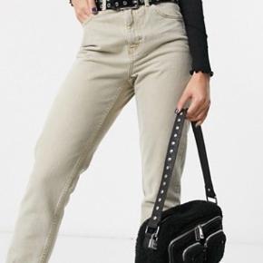 Helt ny og ubrugt skuldertaske / crossbody taske fra Nunoo. Tasken har mange flotte detaljer og så er den lavet i blødt, lækkert bamse / teddybear kvalitet.  Perfekt at matche med en vinterjakke i samme bløde kvalitet eller med en skindjakke.   Tasken har en ekstra, lang og justerbar strop som medfølger, den er også aftagelig.  Og så er der den faste strop med nitter på.   Tasken har ét stort rum med to indvendige lommer, tre lynlåslommer på fronten samt en lille hængelås med nøgle.  En super cool taske i den smukkeste kvalitet. Værdi 700,-