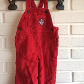 Benetton Baby overall i rødt fløjl. Lækker og blød bomulds kvalitet i 100 % bomuld. Knapper langs benene og skulderen.