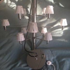 """Sælges for min mor.  """"Ny Herstal Gil 12 Lysekrone i krom med smukke Gil opal glas er en moderne klassiker med de 12 arme og små skærme og har kun gennemgået få justeringer gennem tidens løb. Lysekronen er anvendelig over spisebordet, sofaborde, i halls osv. Lysekronen er med G9 fatninger, så der er ingen transformer, og man kan sagtens sætte LED pærer i lampen så den er meget billig i brug.   Lyskilde: 230V G9 Max 33W. Lampens højde: 56 cm. Lampens Diameter: 65 cm. Ledning: 2 M sort pvc. Da originalstik fra fabrikkens side ikke er skiftet, kan det ses, at den er ubrugt. Der medfølger 2 sæt glasskærme, 12 stk., det ene sæt er med hvid med sorte strøg, det andet sæt er hvidt. Så kan man skifte look. 12 stk. pærer medfølger gratis.   Jeg har givet kr. 4.999 for lampen og kr. 2.148 for ekstra sæt skærme, ialt kr. 7.147. Det hele incl. gratis pærer sælges for kr. 3.800. Seriøse tilbud modtages.""""   Mvh Betina Thy"""