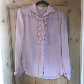 Smuk skjorte med flæser i tyndt og let materiale. Er gennemsigtig. Købt som vintagefund, og mangler to knapper, men fremstår ellers pænt. Passer str. M.