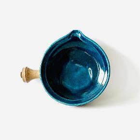 Skål med hank fra Kähler. Glaseret indvendigt med den signatur blå Kähler farve. Signeret af Nils Kâhler, samt mærket HAK Denmark. Højde: 6 cm Diameter: 14,6 cm Længde over hank: 20 cm