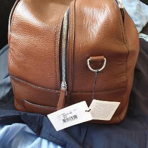 Helt ny weekendtaske fra Tiger of Sweden, model Brome, farve brun.  Weekendtaske fra Tiger of Sweden, fremstillet i præget læder. Tasken rummer ca. 44 liter og er beregnet til 2-3 overnatninger.  • Et stort rum med lynlås. • Tre mindre rum på indersiden, hvoraf det ene er udstyret med lynlås. • Enyderlomme med lynlås. • Udstyret med håndtag, bærerem samt aftagelig og justerbar skulderrem. • Logo på ydersiden. • Rem på bagsiden, som eksempelvis kan fastholde tasken til en håndbagage. • Stofpose medfølger.