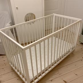 Hvid tremmeseng fra Ikea. Mål 120x60. Har to indstillinger i højden. Den ene side kan tages af.  Følger madras med fra My Baby Dream.