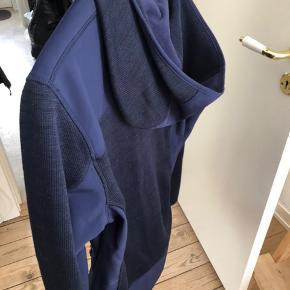 En virkelig flot sports trøje/jakke i mærket Nanok. Lynlås. 3 lommer med lynlås.