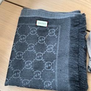 Jeg sælger mit smukke Gucci tørklæde. Det er lysegrå og mørkegrå. Det er købt i starten af denne måned (maj) men jeg har fortrudt farven. Jeg har alt der medfølger (Pose, kasse og kvittering på mail) Det er brugt meget få gange, og står derfor som nyt. Det kan afhentes i Vejle, eller sendes på købers regning (38kr med dao) Det måler W48cm x L180cm