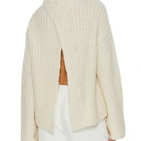 Denne sweater: professionelt look foran og fest bagpå! Denne tykke uldstrik har en høj hals og en lækker, ribstrikket tekstur. Ryggen er åben og draperes som to gardiner. Sweateren er oversize og behagelig, og udskæringen bagpå giver den en sjov og unik detalje. Materiale: 68% alpaka, 10% merinould, 22% polyamid. BEMÆRK: den er aldrig brugt, og har derfor stadig en ulden lugt.  Mål str. XXS: bryst 54cm, længde 61cm, ærmelængde 77cm.