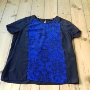 Fin blå/sort silke bluse med knap i nakken og åben til midt på ryggen.