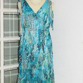 """100 % NY: Lækker kjole i 2 lag. Plissé-""""nederdel"""" og med rigtig flotte skuldre. Materialet er polyester. Farve: Turkis, grøn + sort  Brystvidde: 48 cm x 2 Livvidde: Elastik-liv med vidde mellem 39-47 cm x 2. Længde: inderste lag er 96 cm, og yderste lag er 100 cm   Ingen byt, og prisen er fast"""
