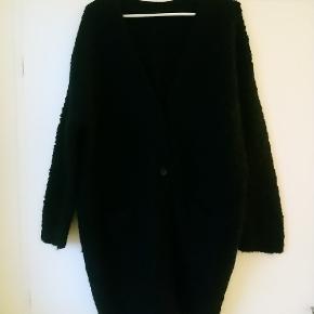 Vamset cardigan fra COS i boucléstrik (100% uld). 2 lommer foran. Længde: ca 94 cm