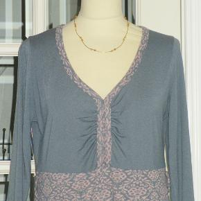 Farve: Dueblå m rosa  100 % NY: Sød kjole med ensfarvet overdel og med blomstret nederdel med blonde forneden. Kjolen har desuden en blomster-brosche (se billede 2), som man kan sætte på eller tage af efter humør. Materialet er 85 % polyester + 15 % viscose. Oprindelig købspris: 600 kr.  Brystvidde: 53 cm x 2 Livvidde: 46 cm x 2 Hoftevidde: 60 cm x 2 Længde: 100 cm   Ingen byt, og prisen er fast