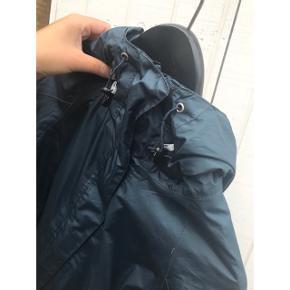 Fin blå regnjakke med hætte og lommer. -brugt få gange.