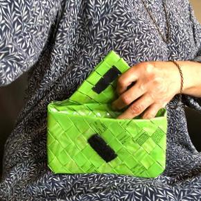 Unik, grøn kuverttaske / clutch med klap.  Flettet i hånden af slikposer fra Carletti.  Klappen holdes lukket med velcro.  Kan også bruges som fx kosmetik-pung.  Bredde ca. 18 cm. Højde ca. 11 cm. Dybde ca. 2,5 cm.  Der findes ingen taske magen til!  Sælges for 175 kr. + evt. porto.  Kan afhentes på Frederiksberg.