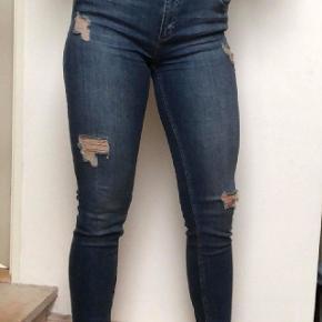 Blå jeans med huller i, aldrig brugt. I bukserne står der at str. er en 30, men det er også M.