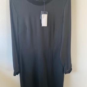 En kjole med mange fine detaljer.  -Ærmer i let stof -krave og afslutning på ærmer i fløjelsstof  Str 10 i Hilfiger str