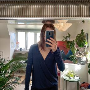 """Mørkeblå trøje med nedringet ryg, som dog kan vendes til at være nedringet foran. Blødt, glat stof.  Med skjulte """"låse"""" ved skuldrene, hvor ens bh kan sættes fast i, så trøjen holder sig oppe."""