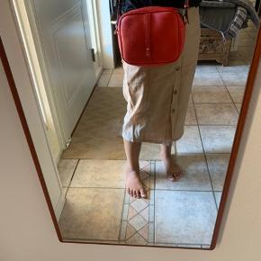 Decadent Polina Round rød taske. Brugt 1 gang.  Fremstår som ny.   Har 1 stort rum og et lille inde i. Remmen kan justeres.  Måler 25 cm i længde