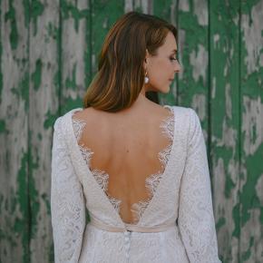 Jeg sælger min brudekjole 2020. Kjolen er skræddersyet hos Karim Design og renset, så den står som ny (se billeder). Tasken medfølger. Værdi: 17.500  Kjolen passer str. ca. 38.   Kjolen har en smuk nudefarve i underkjolen, flotte blonder og kimono-ærmer. Og så fremhæver den bryst og ryg og resten af figuren.  Den har været på til første del af vores bryllup, men for at passe på kjolen skiftede jeg før brudevals og fest. Den er allerede renset og står som ny.   Mål:  Kjolen passer lige nu en på 170cm i højde, med en mindre hæl (5,5 cm).  Talje (ved bånd) ca. 34 cm  Bryst (armhule til armhule): ca.,37 cm  Hofte: ca. 43 cm