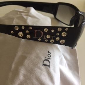 """Flotte solbriller fra Dior med """"diamanter"""" som glimter helt vildt i solen. Glasset måler: 6 cm i længden og 3,4 cm i højden. Tjek evt. mål med et par af dine egne solbriller. Der er en mikroskopisk lille ridse i det ene glas. Det er ikke noget man kan se når man har solbrillerne på. Jeg tager ikke billeder med brillerne på. Jeg har ikke det originale etui men der kan medfølge et etui fra Apair MP 250,00 pp"""