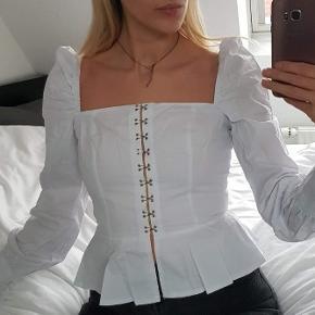 Smuk bluse med hægter til at lukke. Minder om bustier / korset style i snittet. Square neck og talje. Lette pufærmer.   Brugt 1 gang