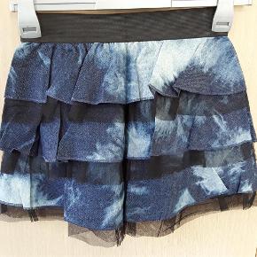 FEJLLEVERING. Sød ny nederdel i denim og tyl, syet i etager, med elastik i livet. Livvidde 68-76 cm. længde 37 cm.  NY NEDERDEL Farve: Blå