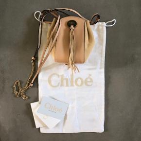 Chloe Suede Calfskin Drawstring Blush Nude. Fineste lille Chloe taske i perfekt stand.  Inkl. dustbag og ægthedsbevis.  Obs farven er nærmere nude, ikke beige.   Hentes i Farum eller sendes med DAO på købers regning og mod forudbetaling. Evt. TS-gebyr på købers regning.