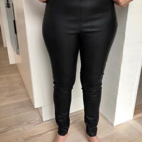 Virkelig fine læder bukser fra Part Two i str. 38. Forsiden er lavet af kunstlæder og bagsiden er 66 % viskose, 30% polyamid  og 4 % elastik og er derfor stof som er elastisk. De er brugt, men fortsat pæne. Nypris 1000kr. De er super lækre at have på og lukkes med lynlås i siden.