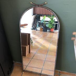 Gammelt butiksspejl i tungt metal. Kan både stå eller hænge. Samlet højde er 93 cm. Bredden er 44 cm.