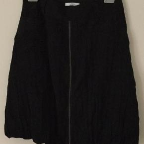 Fin sort nederdel i det lækreste lette stof. Nederdelen er foeret, med to lommer i siden og lynlås helt igennem. Livvidde 42 x2 cm og længde 60 cm.  Køber betaler Porto med 45 kr.