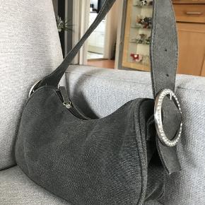 sød lille taske i gråt denim stof Der mangler ingen af stenene på spændet. den er 12 cm på det laveste sted og 26 cm bred. Hanken kan indstilles