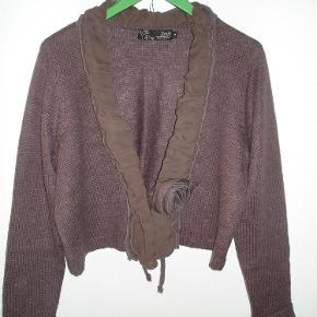 """Varetype: Cardigan, kort, flot detalje med 30% uld Farve: Støvet lyng  Kort cardigan, åbentstående med indvendigt bindebånd til at holde den lukket - hvis dette ønskes. Vidunderlig flæseagtig detalje i andet materiale langs forkanten hele vejen rundt. Slutter med en """"rose"""". Indeholder 30% uld. Måler over brystet 114 cm. Længden er 48. cm. Er brugt et par gange og fremstår i flotteste stand. BYTTER IKKE!!"""