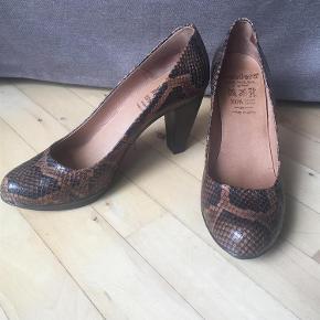"""Varetype: Pumps / heels / stilletter Farve: Sort/brun  De lækreste, mest feminine, elegante og komfortable sko fra Wonders sælges. Kender du mærket, kender du også kvaliteten.   100% comfort leather. """"Puder"""" nede ved forfoden, så den er blødere at gå i. Gummisål, der gør den blød og fleksibel. Sål og indvendigt er det blødeste skind, så man ikke får fugtige/svedige fødder.   Hælhøjde 9 cm. Plateau 1 cm. Indvendig længde 25,5 cm.  Se også mine andre annoncer.   Handler også gerne mobilepay.   Hvis andet ikke fremgår af et evt. bud, anses buddet for værende ekskl. gebyrer og porto.   Jeg sender med DAO og portoprisen er sat derefter.  Jeg forudsætter, at betaling finder sted senest 24 timer efter, at vi har indgået aftale, medmindre andet er aftalt. Husk at bud er bindende på TS :-) Manglende overholdelse af aftale vil medføre anmeldelse. Jeg har desværre haft for mange useriøse """"købere"""", og det er synd, hvis det skal ødelægge det for dem, der er seriøse."""