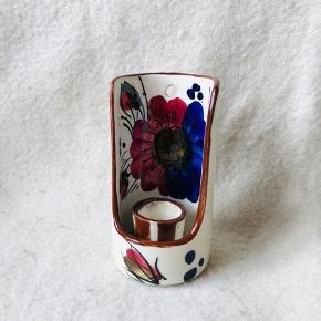 Skøn rund lysestage i porcelæn med fantastisk blomstret glasur. Kan hænges på væggen.  Ca 11,5 cm høj  Udsmykningen ligner noget fra Hedebo keramik. Der er dog intet stempel.