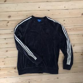 Mørkeblå velour tracksuit trøje fra Adidas. Størrelse medium.  Jeg har også de matchende joggingbukser til salg, så det kan blive et sæt. Begge dele kan købes samlet for 700,-