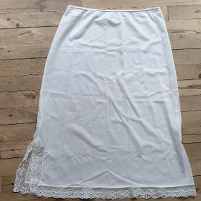 Vintage, retro underskørt i fin stand af mærket Südtrikot. Det måler 70 - 90 i taljen, 106 om rumpen og det er 70 langt.