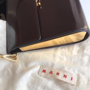 Den er i fin stand og ingen ridser på guldsiderne. Super fin bourdeux Marni taske, med guld sider.   Den er 24 cm lang, 20 cm i højde og 6 cm i bredde målt på den bredeste stykke forneden.  Der er dog et lille trykmærke bag på, som man ikke ligger mærke til ved brug.