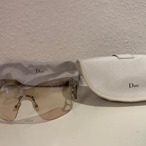 Super cool Dior solbrille med krystaller på siderne i det klassiske D og i mærket nederst under venstre øje💎 glassene er bøjede og følger ansigtet og er lettere gennemsigtig, hvilket giver et fedt look👌 solbrillerne er brugt få gange, så fremstår derfor i super stand- alle sten er intakte og originale ekstra sten medfølger også solbrillerne🤩 herudover medfølger originalt brille etui og pudseklud. Et par super fede solbriller i fantastisk stand med alt tilbehør til🌸 hvem skal være den heldige🌞