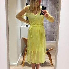 Flot gul Baum und Pherdgarten kjole. Den har en underkjole og en overkjole i mesh med prikker, bindebånd og lange ærmer. Der står ikke størrelse i, men den svarer til en str 36/38.