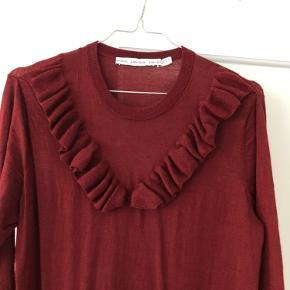 Fin knælang kjole i 100% uld med flæsedetalje på brystet.