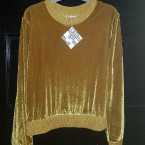 Super lækkert bluse i velour. Farven er gul, med skær af guld. Den er med mærke. Sælges for 400 kr.