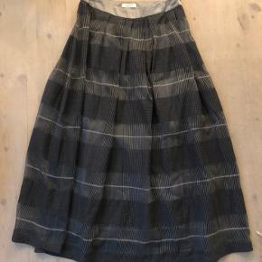 Lang nederdel i gråt mønster fra italienske Peserico. Uld og silkeblanding. Længde: 95 cm.