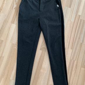 Grå bukser fra The Nordic med sort kant ned langs benene.